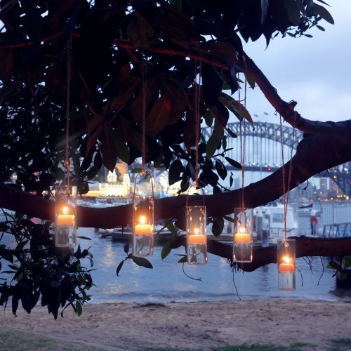 Hang beeswax tealight candles in glass holders in a tree for beautiful magical light