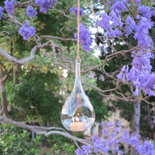 Glass teardrop candle holder with bee wax tealight candle in clear cup with a happy flame