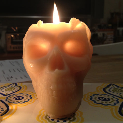 Beeswax skull candle with eyes aglow as it burns