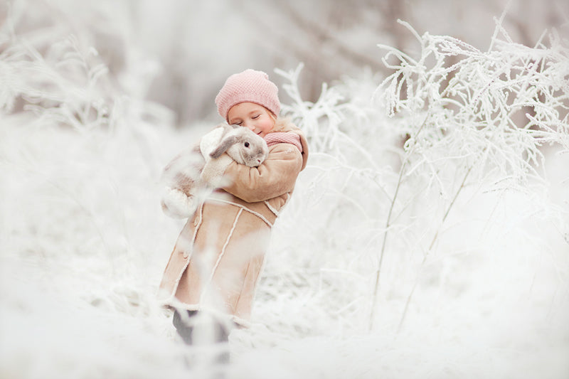 Little girl holding cold rabbit in snow.