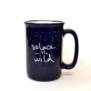 Blue ceramic Solace in the Wild mug with white writing and white speckles.