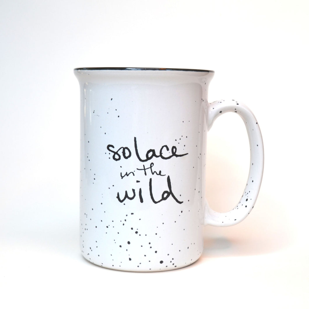 White ceramic Solace in the Wild mug with black writing and black speckles.