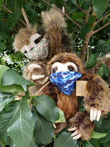 Two large plush sloths sitting in a tree wearing masks, one mask with blue shark outlines, one with sloths and flowers