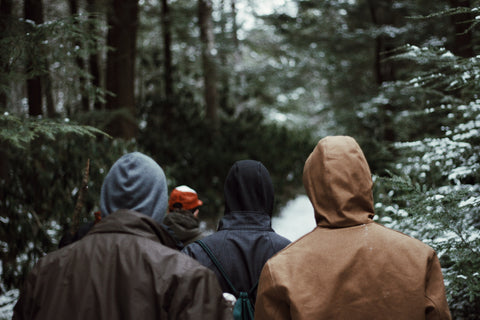 four men walking through a snowy Forrest.