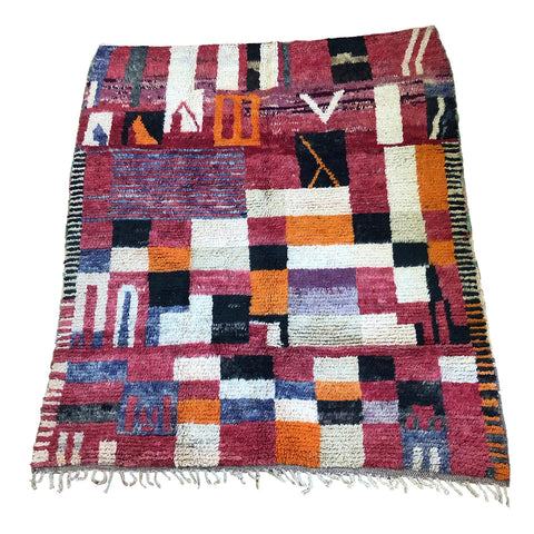 Colorful red, purple, and orange blocks on Moroccan rug with abstract and geometric design