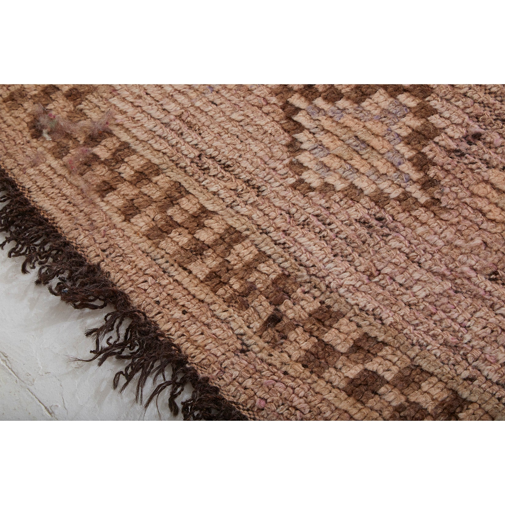 Detail of vintage Moroccan berber rug with brown goat hair fringe