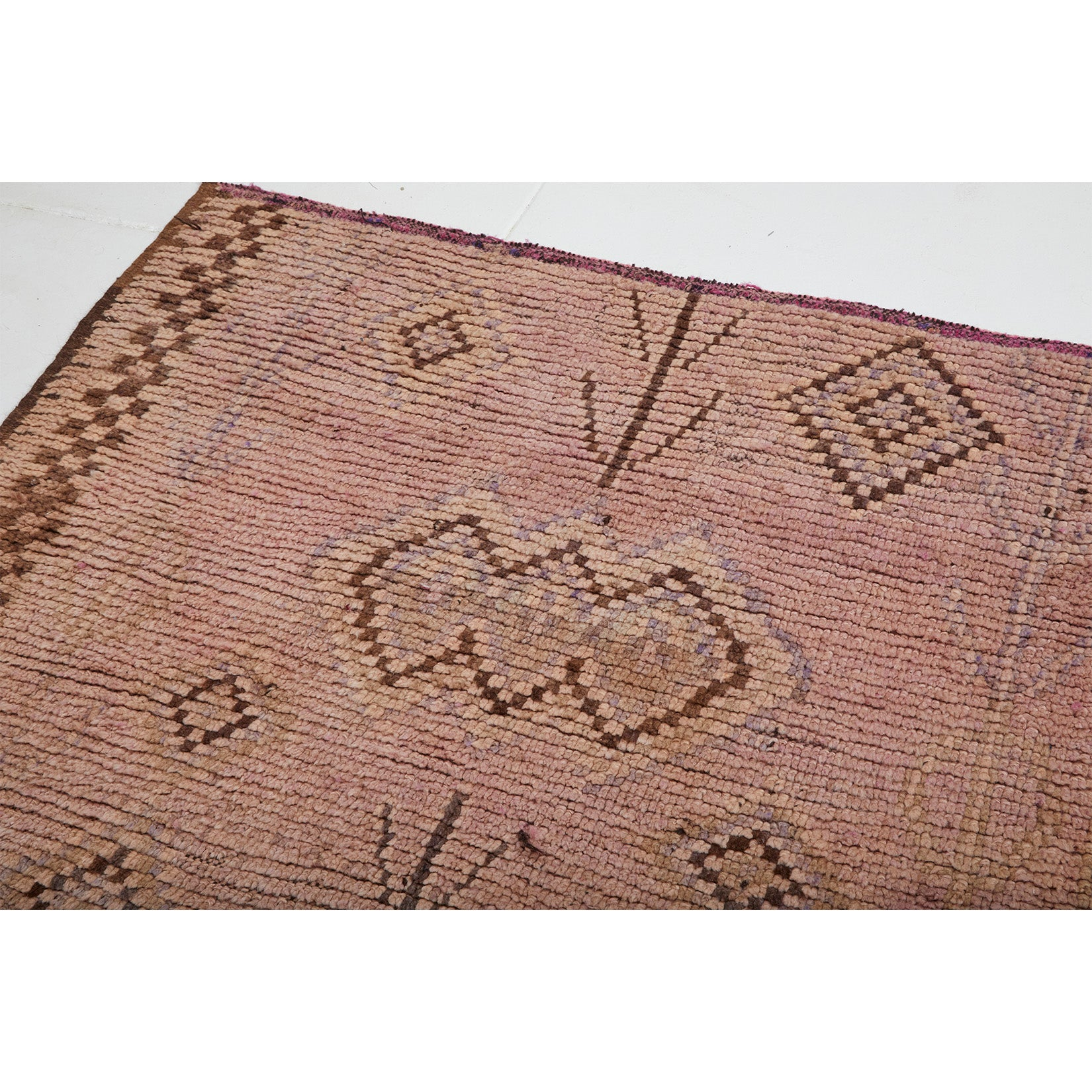 Detail of checkerboard vintage Moroccan rug with abstract diamond designs in brown and faded colors