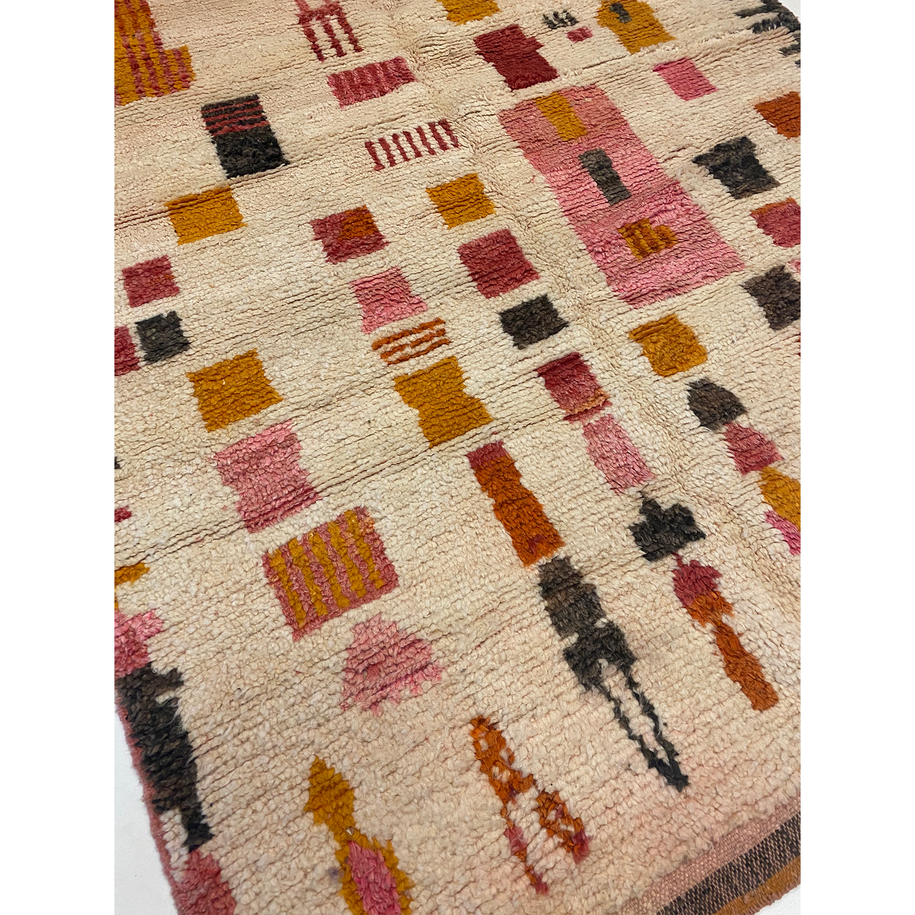 cream-colored Moroccan rug with designs in blush pink and mustard yellow