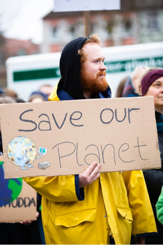 man holding save our planet sign