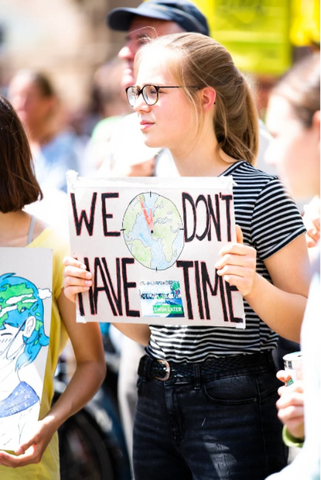 girl holding sign that says we don't have time