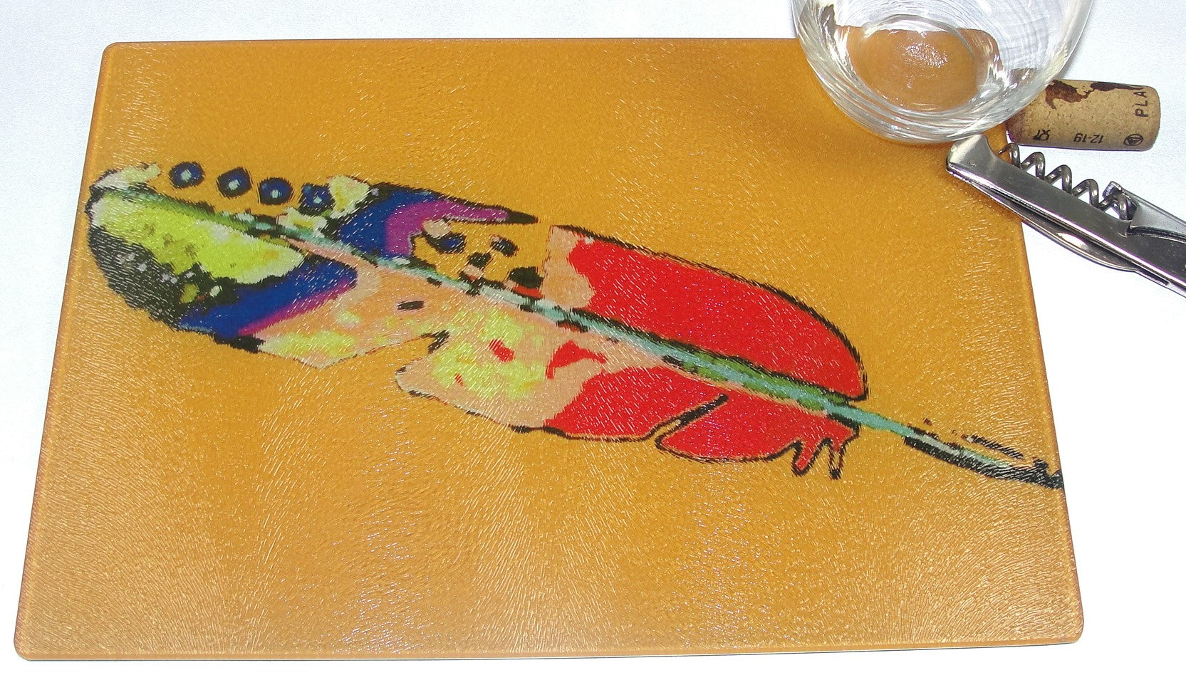 Cutting Board, Glass, Feather on Orange Background