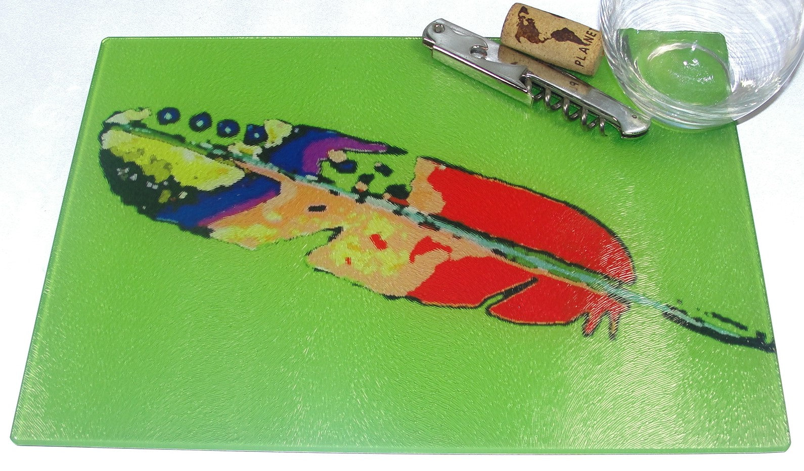 Cutting Board, Glass; Feather on Green Background