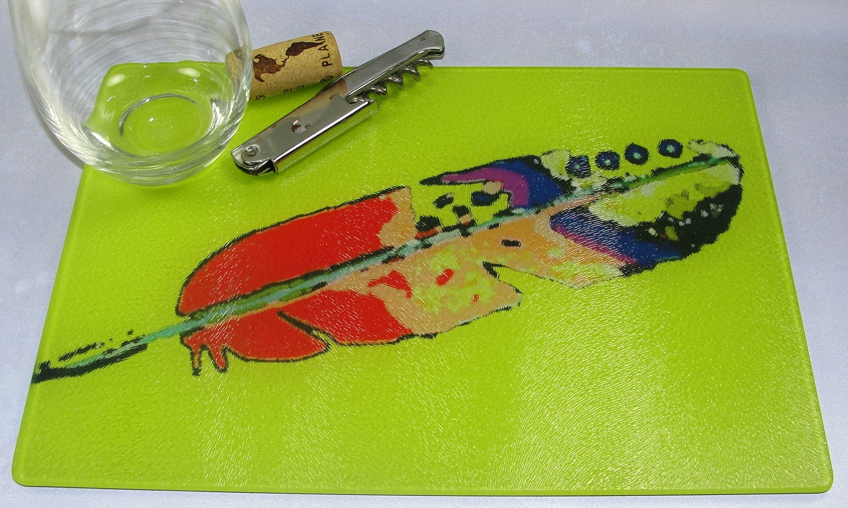 Cutting Board, Glass; Feather on Yellow Background