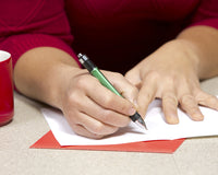 person writing on a card with a pen