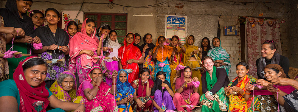 Nicole Snow, Founder of Darn Good Yarn and Good Sol poses with a group of artisans in India.