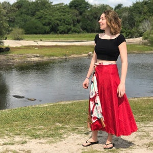 woman wearing a red bright skirt with a lake in the background