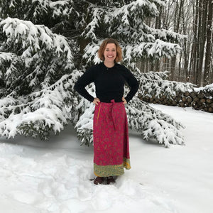 woman standing outdoors surrounded by snow and wearing a bright red sari wrap skirt