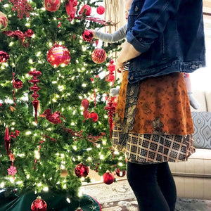 woman wearing a sari wrap skirt while hanging ornaments in the Christmas tree