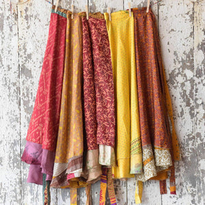 five sari wrap skirts hanging over a vintage wall
