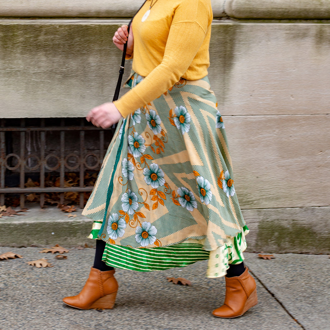 Close up of woman walking on a side walk wearing a green yellow and white sari skirt