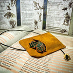 Light brown leather dice bag with green metal dice on book - Dice Bags - Questing Tools
