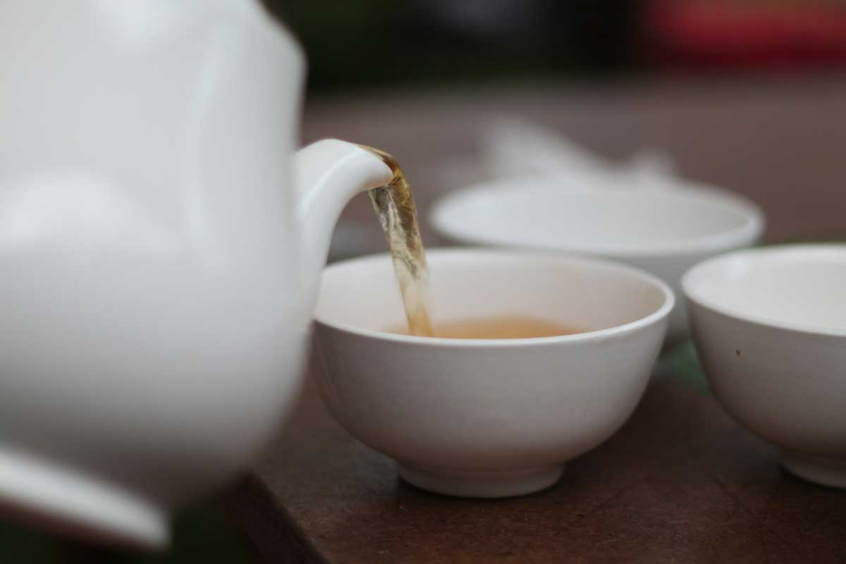 Pouring green tea into a cup