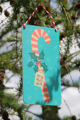 Red Stripe Candy Cane on Blue Wooden Sign.