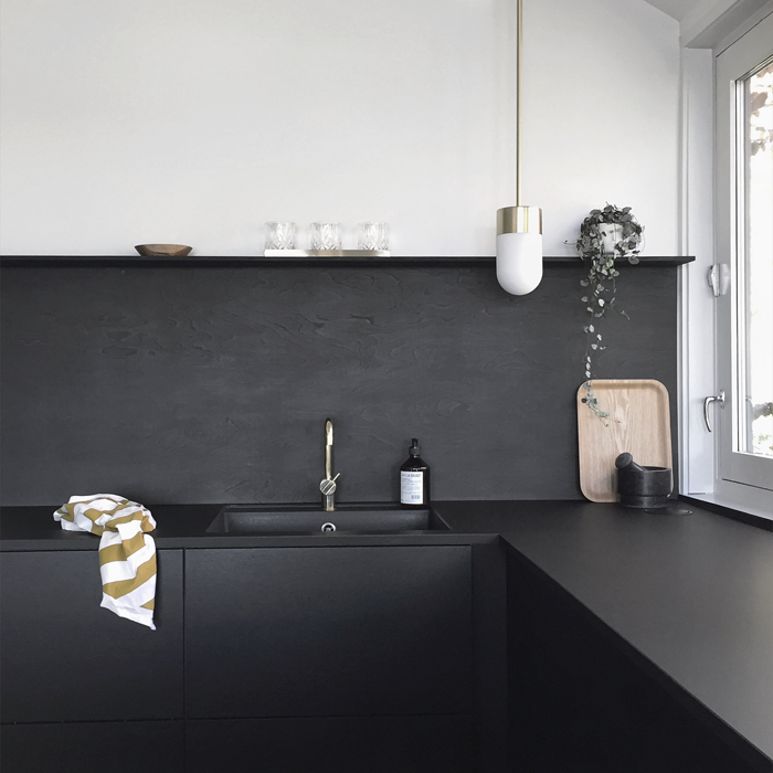 Minimal modern Scandinavian style kitchen with black walls.