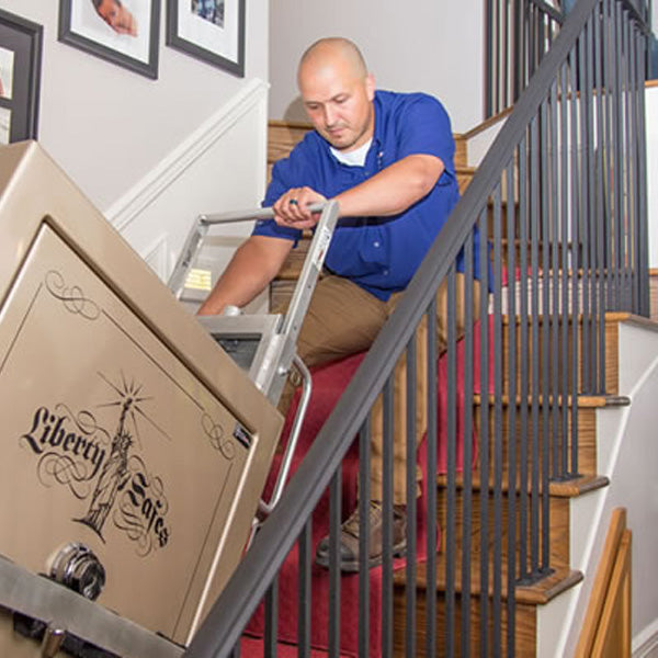 Man delivering safe upstairs