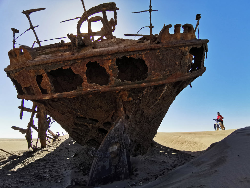 Riding fat bike past ship wreck in Namibia