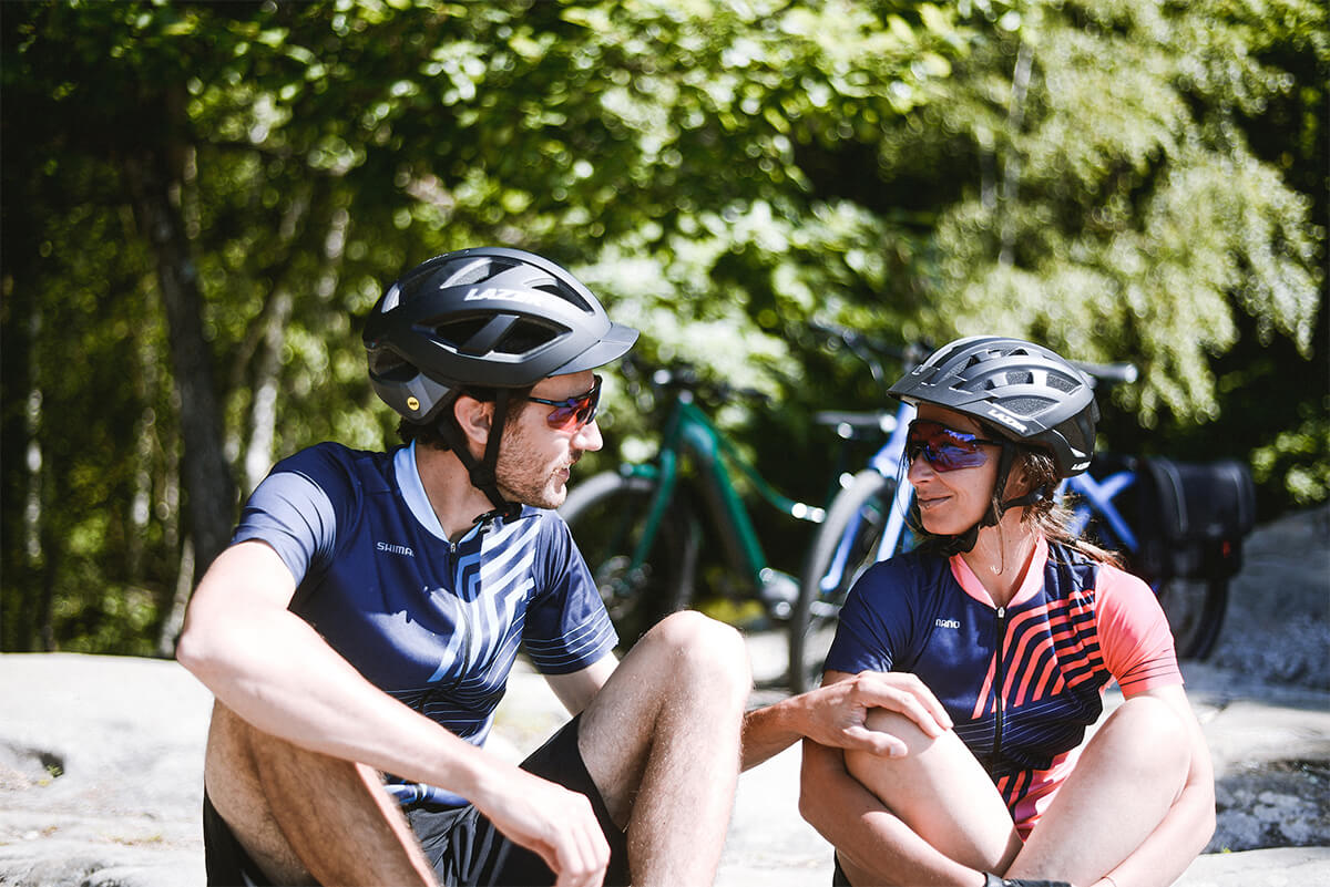 Couple wearing a Lazer Cameleon MIPS helmet and lazer Compact DLX MIPS helmet while riding ebikes
