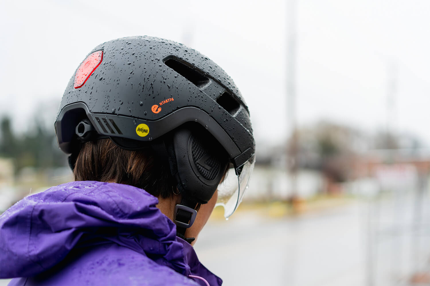 Women wearing a Lazer Urbanize MIPS urban bike helmet with Lazer LED Taillight in the rain while commuting to work.