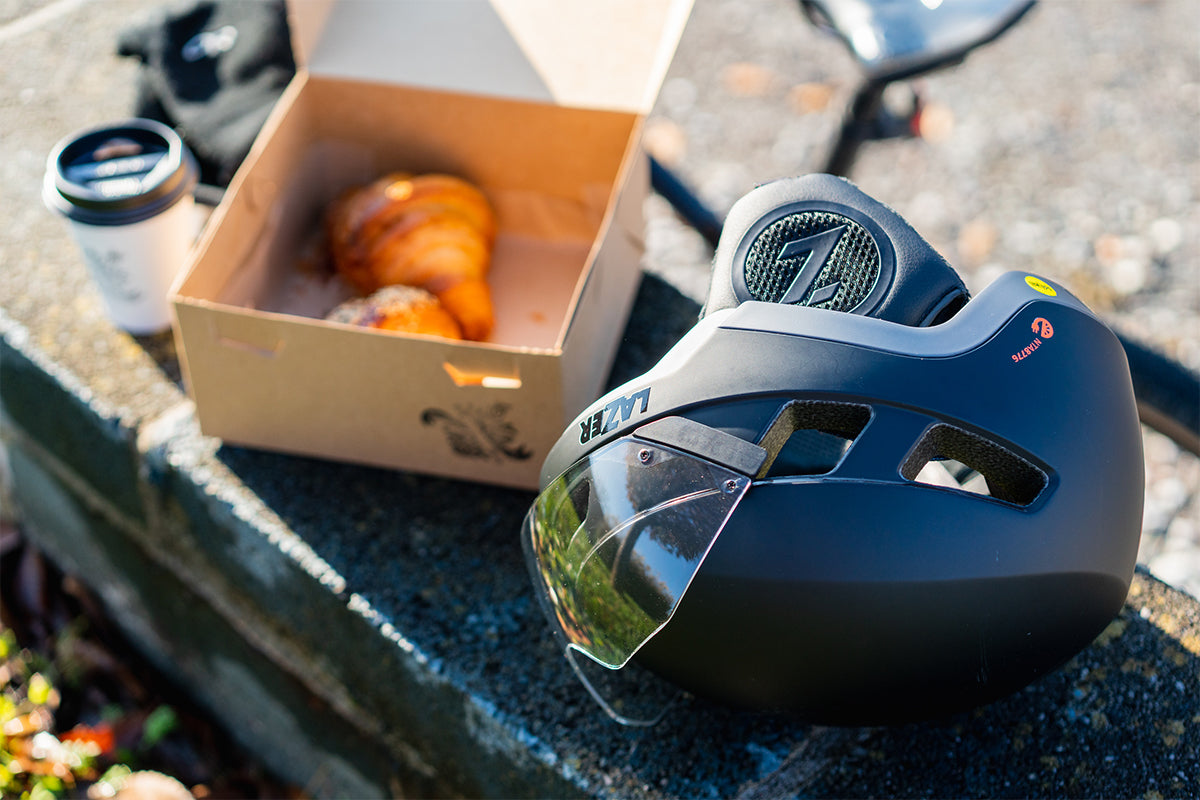 Lazer Urbanize MIPS helmet sitting next to a box of croissants and coffees