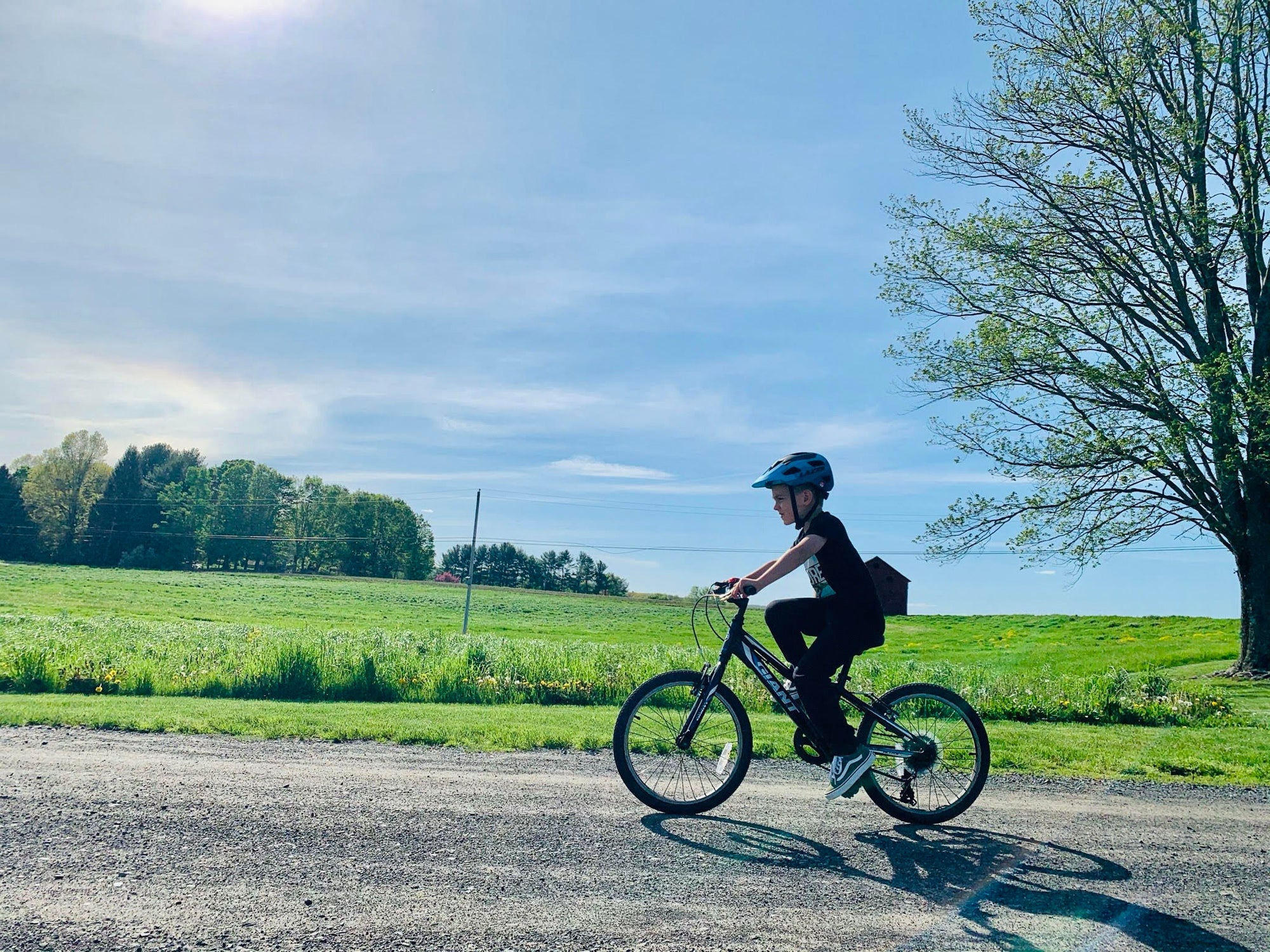 Young kid riding his bike with a Lazer kids helmet on a sunny day