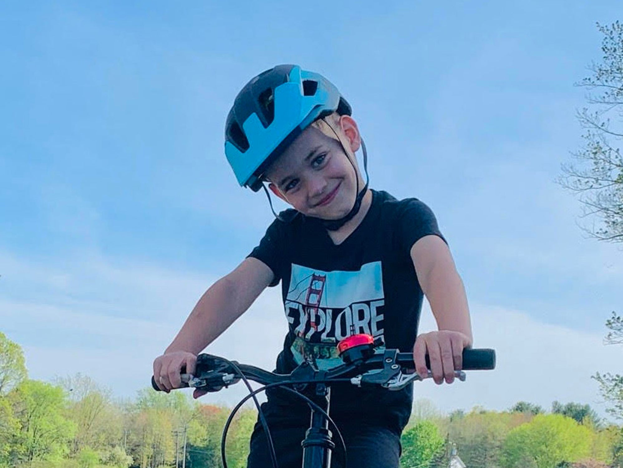 Young boy smiling as he ridings his bike while wearing a Lazer Kids helmet