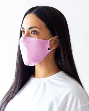 Pink solid cloth face mask modeled on a female