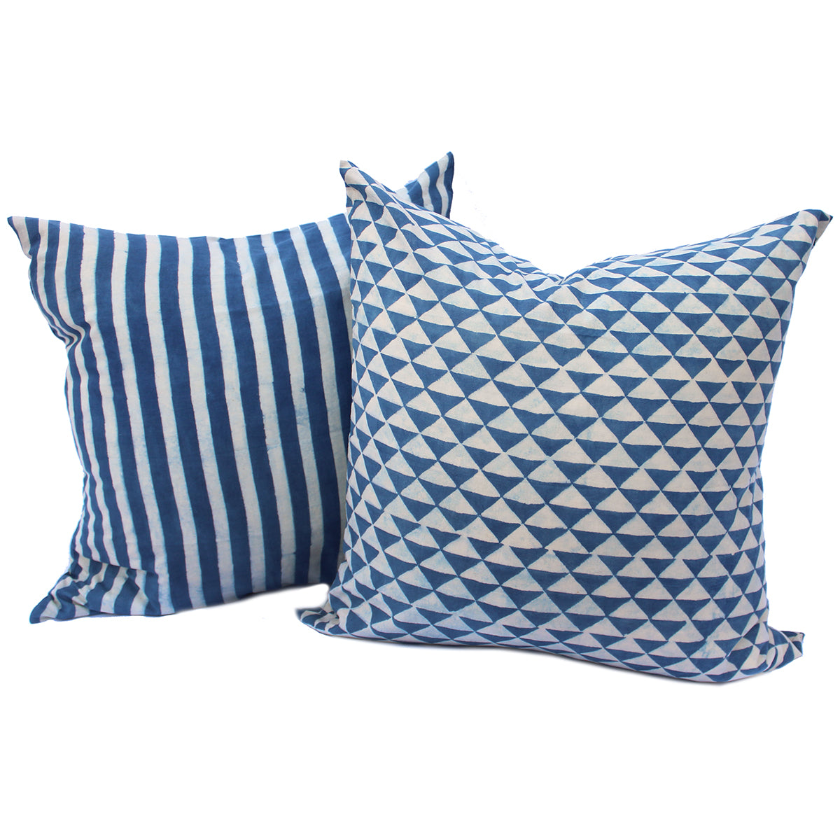Decorative set of two indigo dyed pillow made using fabric printed by hand and indigo dyed in Kutch, India. One pillow is dyed in deep indigo with white stripes the the second has an indigo dyed geometric design. Both pillows have a cool, nautical feel. Pillow covers are 100% cotton and inserts are natural feathers.