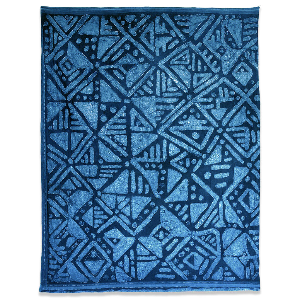 Indigo dyed rectangular quilt with aztec design in varying shaded of indigo. Indigo dyed using hand-painted paste resist, this handmade quilt has been lovingly and expertly hand stitched. Canopy incorporates a mixture of shibori and hand-painted surface treatments with free-style top stitching. Created using 100% cotton bedsheets, the quilt also has decorative tassels along the edge to make use of any leftover fabric.