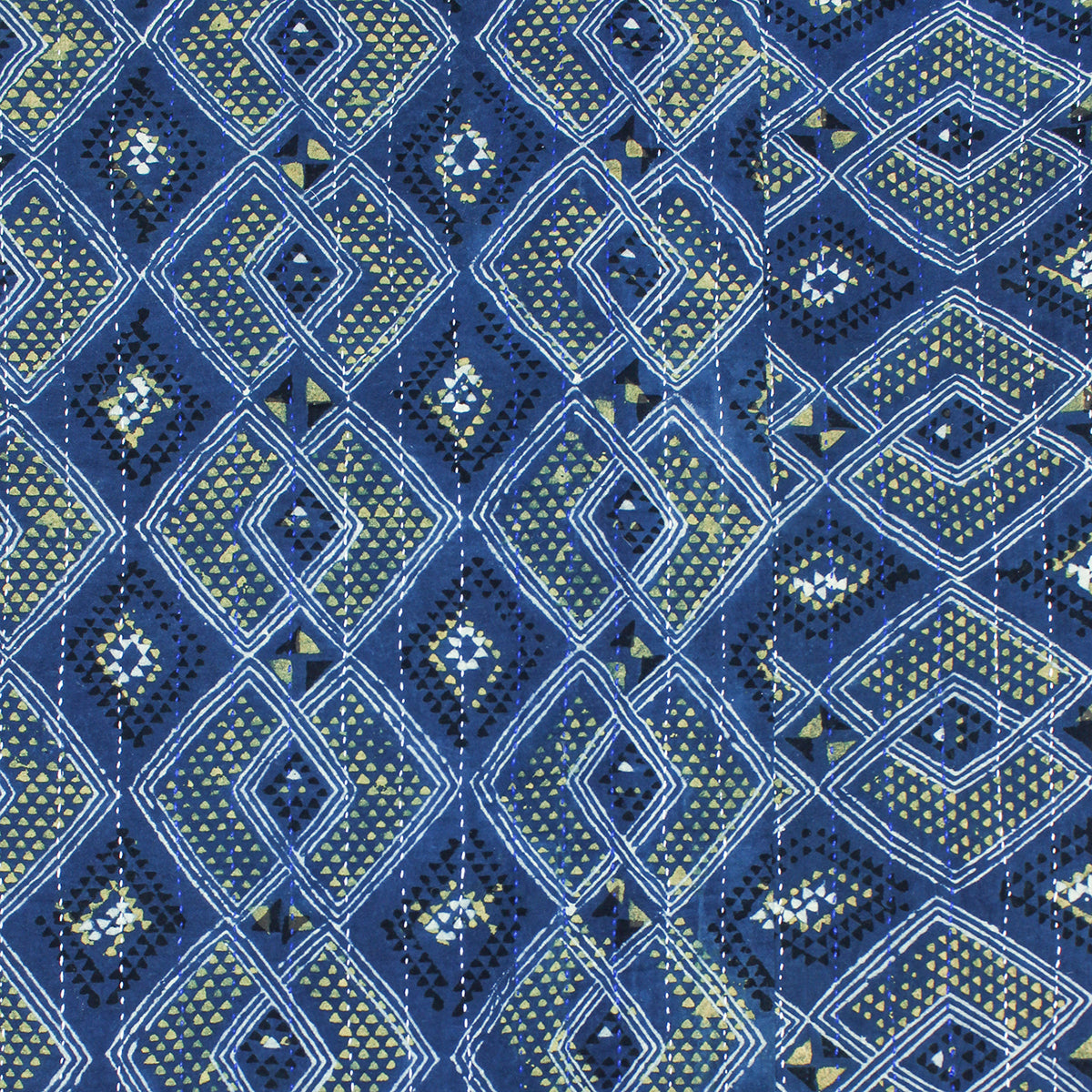 Detail of reverse stitching on indigo dyed woven quilt showing diamond shapes overlapping with intricate detailing in each