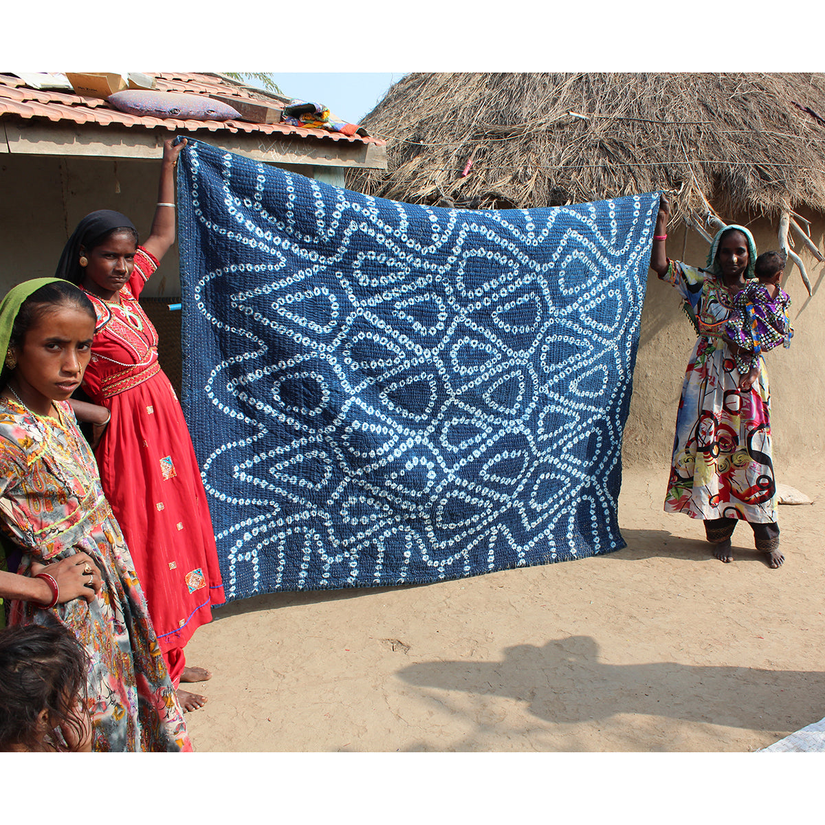 Two women holding up indigo dyed woven quilt