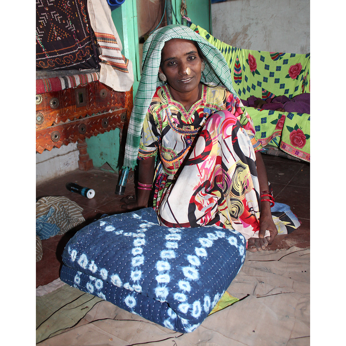 Indian women draped in colourful fabric wearing indigo dyed quilt over her lap