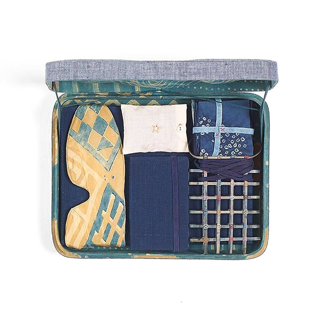 Essentials blue case containing blue and cream eye mask, indigo diary and four stacked handkerchiefs.