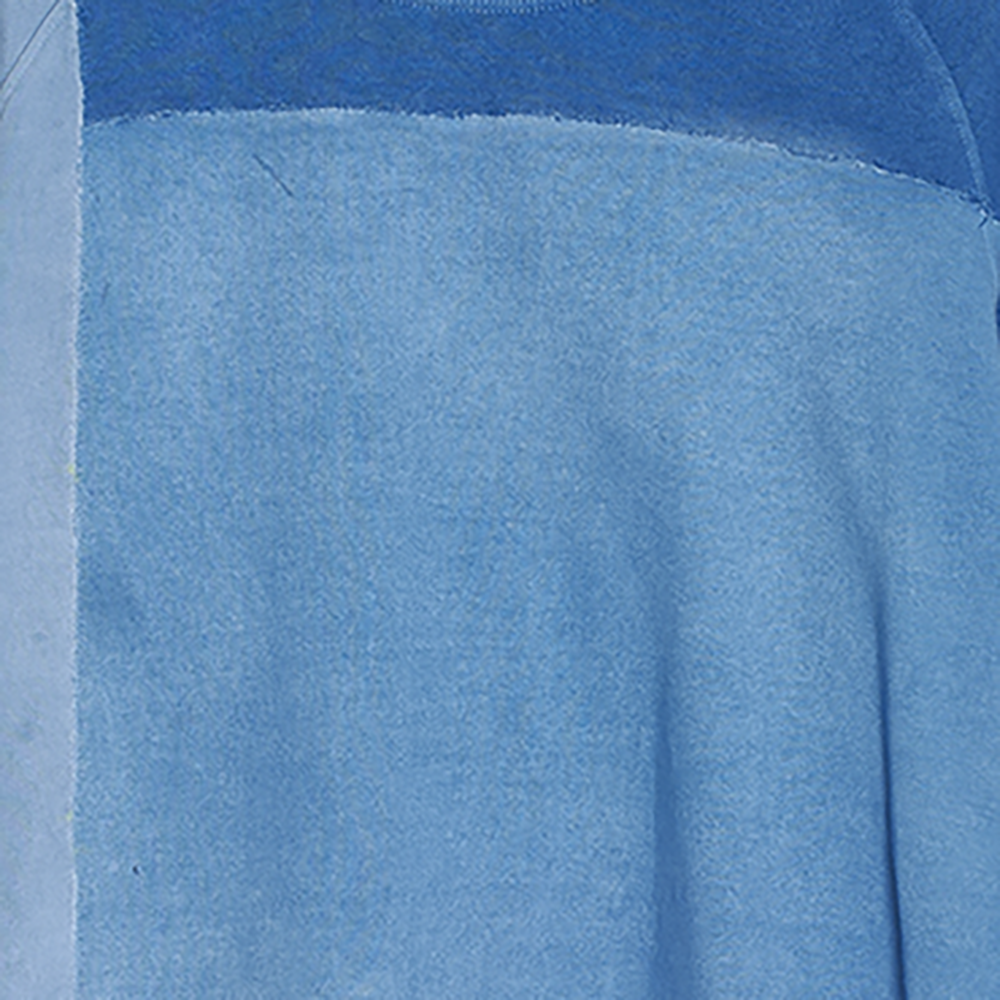 Detail of patch on mens loose fitted sweatshirt in shades of indigo