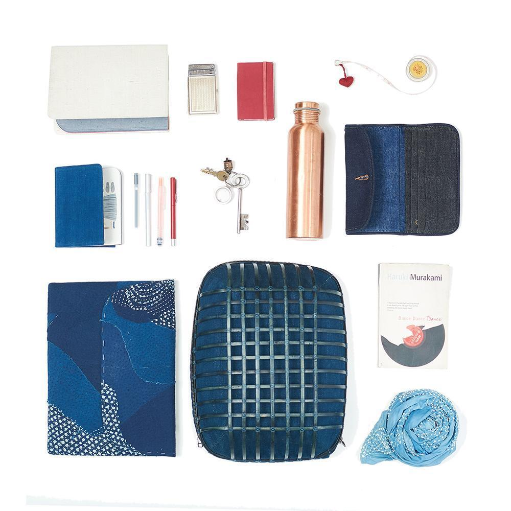 Array of items including indigo backpack, copper water bottle, indigo notebook and blue scarf