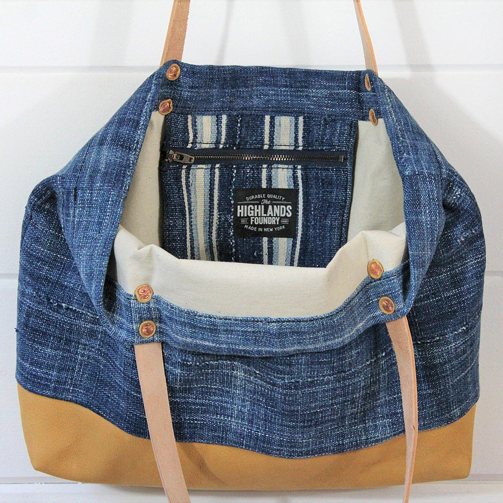 Interior zipper pocket and label of indigo cloth tote bag with tan Deerskin straps and bottom.