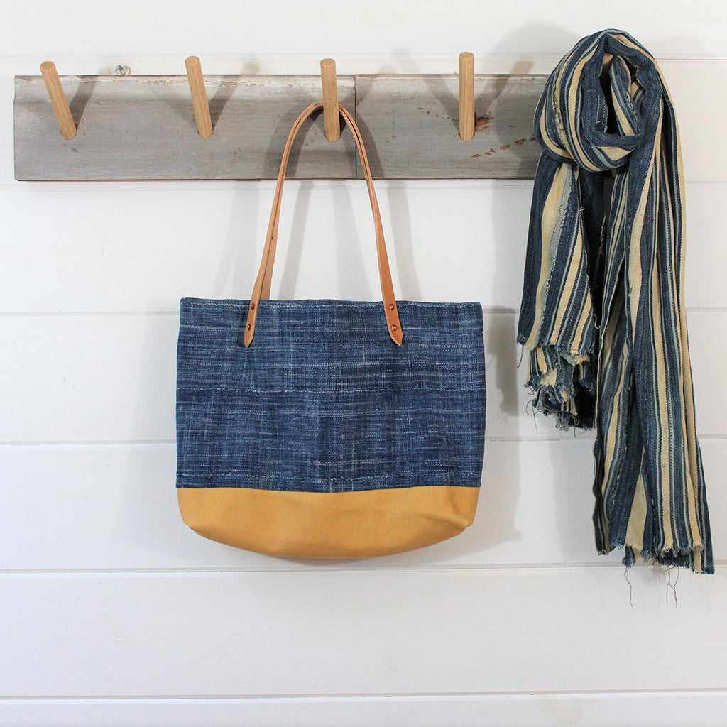 Indigo cloth tote bag with tan Deerskin leather straps and bottom. Displayed on wooden hook alongside blue and tan linen scarf.