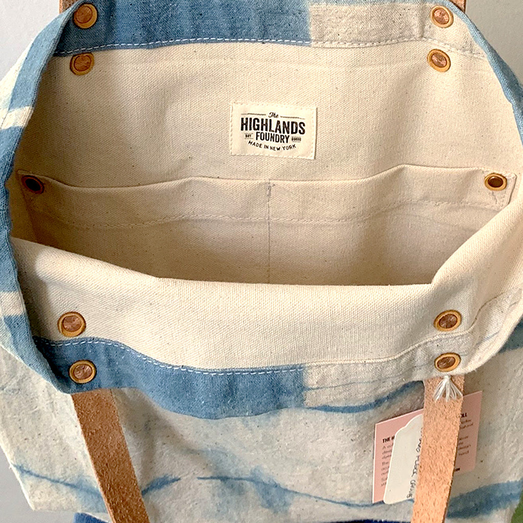 Interior and label of Indigo and cream Shibori dyed canvas tote bag with tan leather straps.