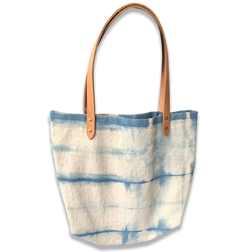 Indigo and cream Shibori dyed canvas tote bag with tan leather straps.