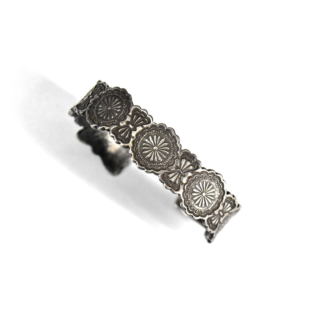 silver bracelet bangled carved to look like concho belt.