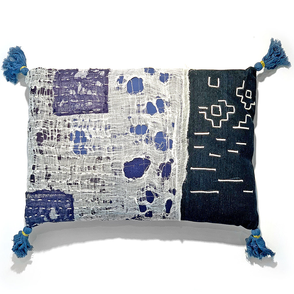 indigo and white decorative throw pillow with tassled blue corners